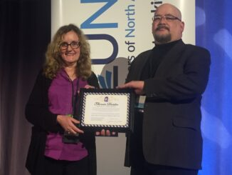 Marcia Barrett receives award from Michael North